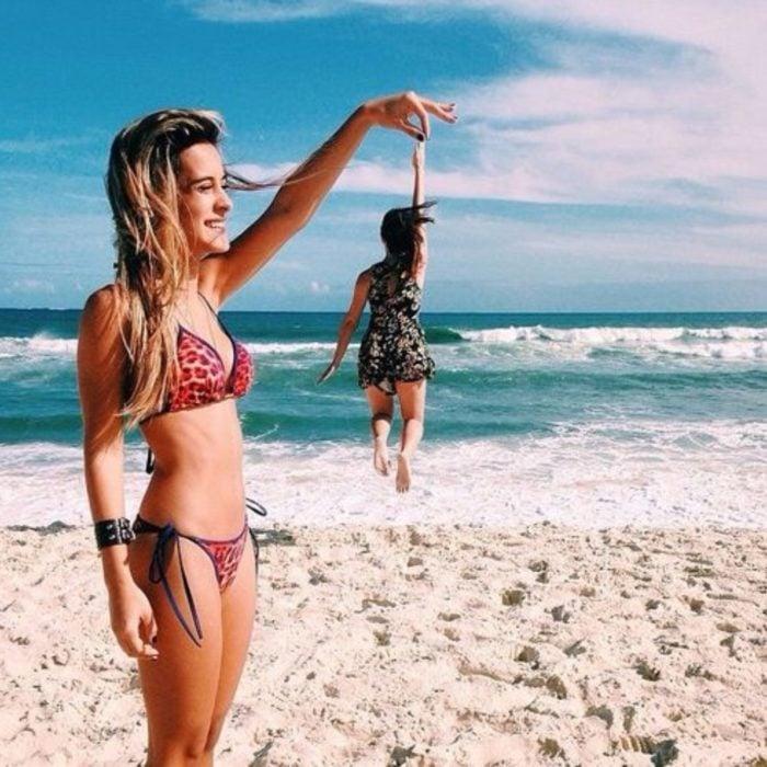 Mejores amigas en la playa tomándose una foto en la que simulan estar sosteniéndose de la mano