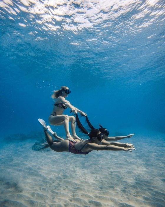 Chicas buzeando en el fondo del mar y dando la ilusión de que una está montando a otra como si se tratara de un delfín