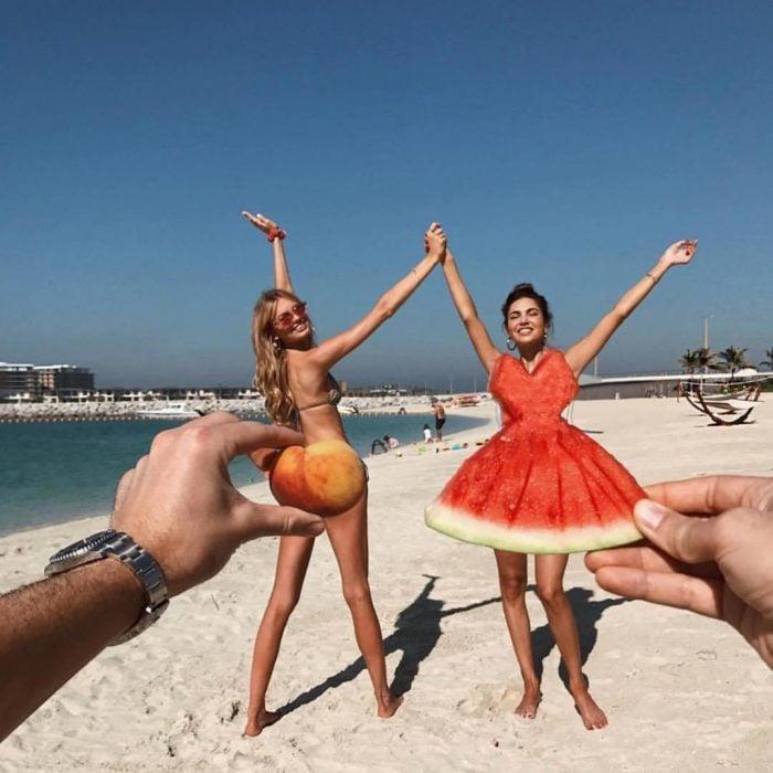 Chicas posando en la playa con un durazno que da la ilusión de ser un traje de baño y una sandía cortado como si fuera un vestido