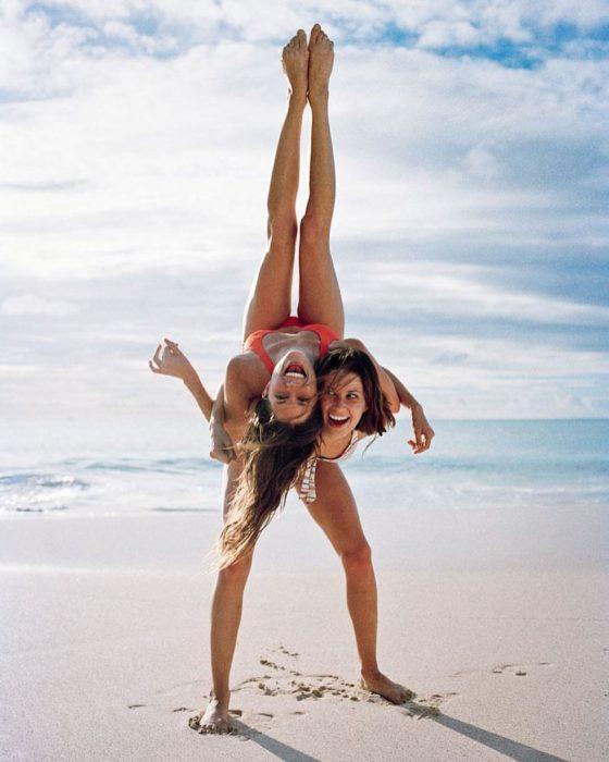 Foto de mejores amigas en la playa practicando Yoga en la playa
