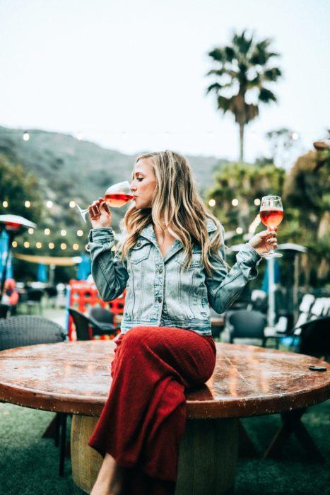 Chica sentada sobre una mesa bebiendo vino tinto delicadamente