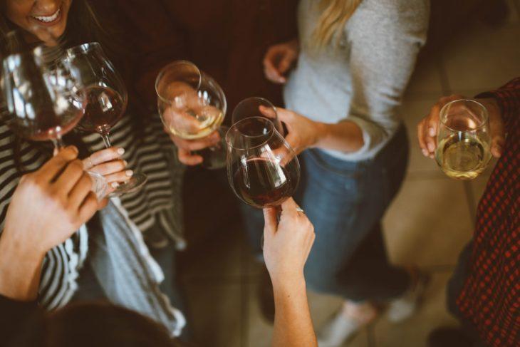 mujeres brindando, chocando sus copas de vino tinto durante una celebración