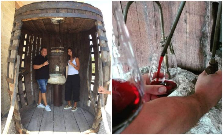 Hombre y mujer dentro de un barril gigante bebiendo vino tinto