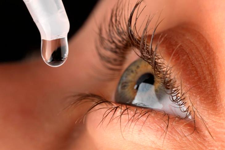 Un ojo verde en primerísimo primer plano echándole una gota