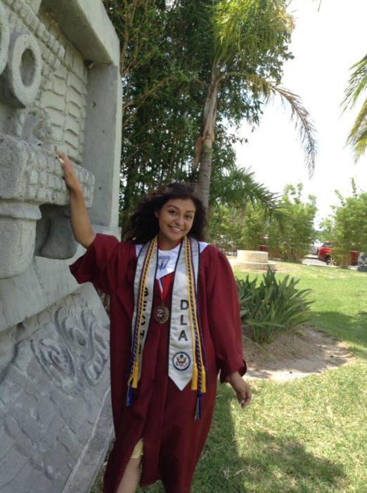 Saraí Ruiz vestida con su toga de graduación luego de la ceremonia en la que recibió su certificado