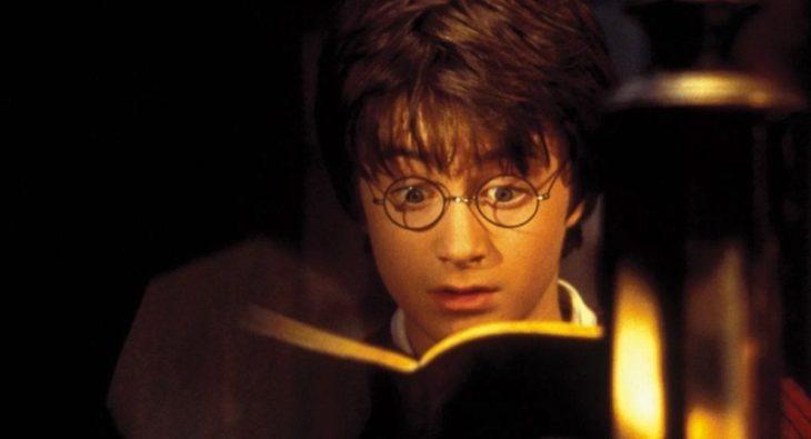 Harry Potter leyendo un libro abierto, mientras se ilumina con una vela, escena de Harry Potter y la piedra filosofal