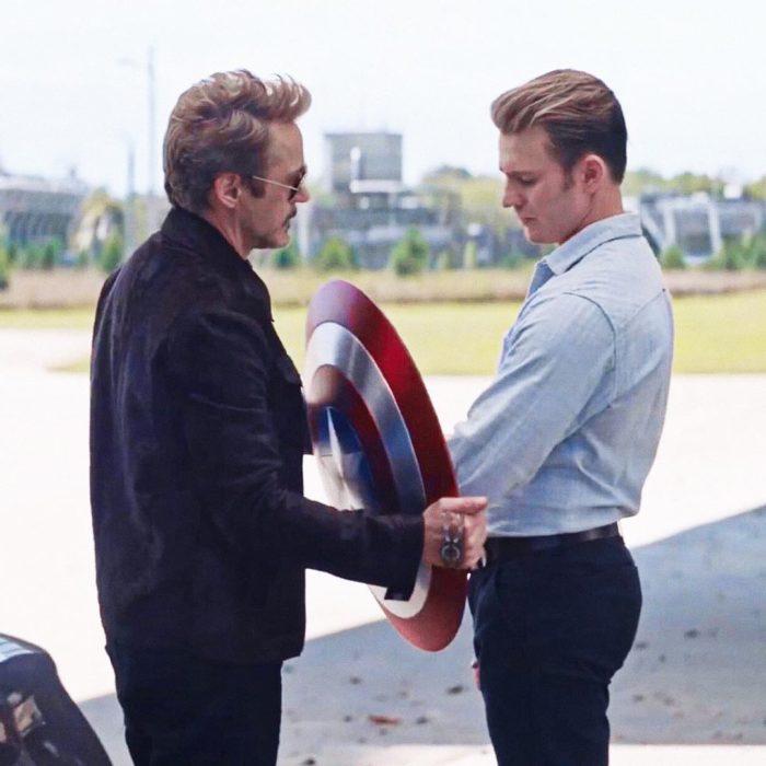 Chris Evans y Robert Downey Jr. charlando mientras sostienen el escudo de Capitán América, Avengers