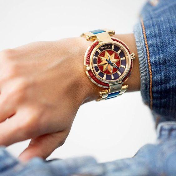 Reloj metálico con decoraciones en azul marino, rojo y amarillo, joyería inspirada en Marvel
