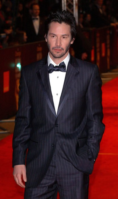 Actor Keanu Reeves, hombre en alfombra roja con traje negro y moño