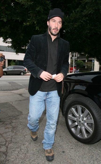 Actor Keanu Reeves, hombre caminando en la calle con gorra y saco negro, y pantalón de mezclilla