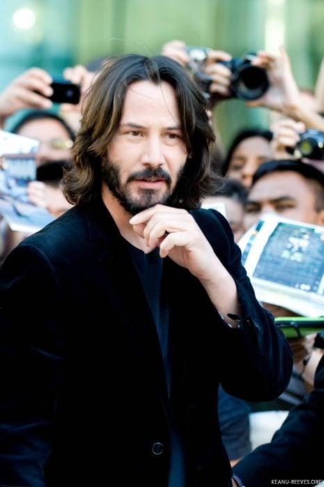 Actor Keanu Reeves, hombre con cabello largo y barba, traje de vestir negro