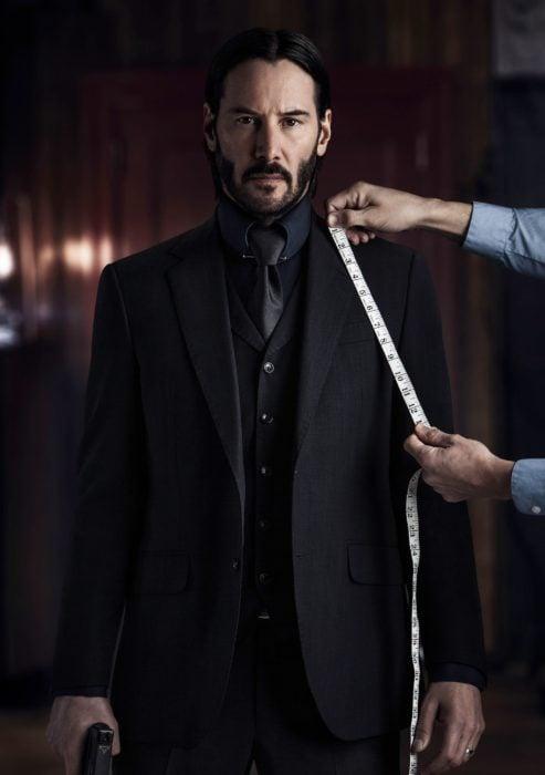 Actor Keanu Reeves, película John Wick, persona midiendo su traje negro; hombre con cabello negro, largo y barba