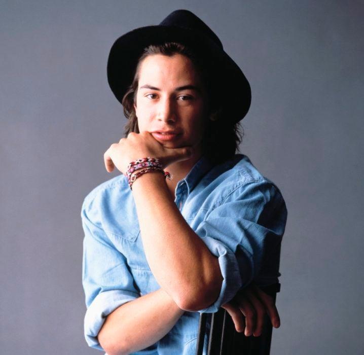Actor Keanu Reeves; joven con camisa azul, sombrero negro y cabello largo