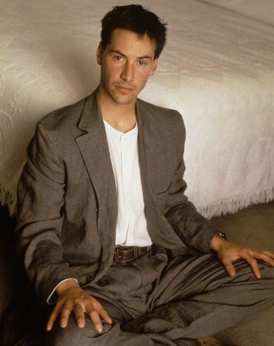 Actor Keanu Reeves joven; hombre sentado en el suelo con traje café