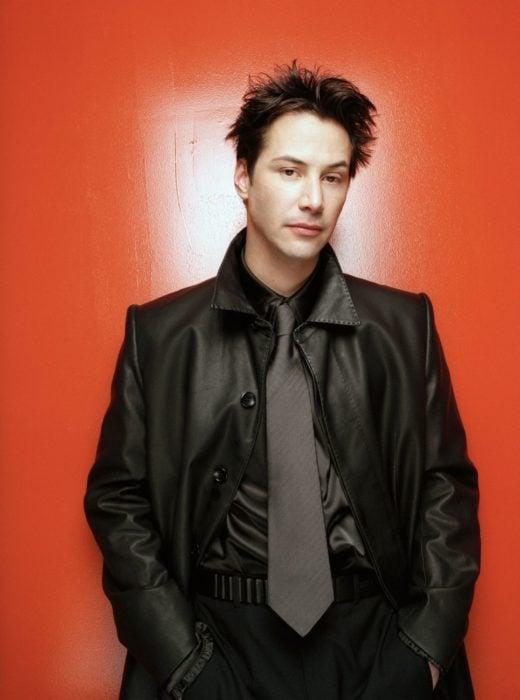 Actor Keanu Reeves joven, hombre posando para foto con traje negro y cabello corto