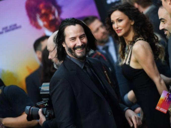 Keanu Reeves sonriendo durante un evento de alfombra roja