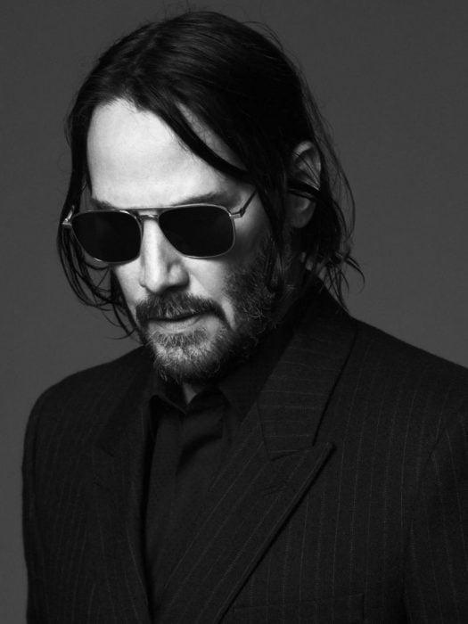Keanu Reeves con cabello largo y gafas oscuras mirando hacia abajo mientras modela para la nueva campaña de Saint Laurent
