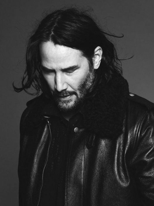 Keanu Reeves con cabello largo y barba desalineada mirando hacia abajo y modelando para Saint Laurent