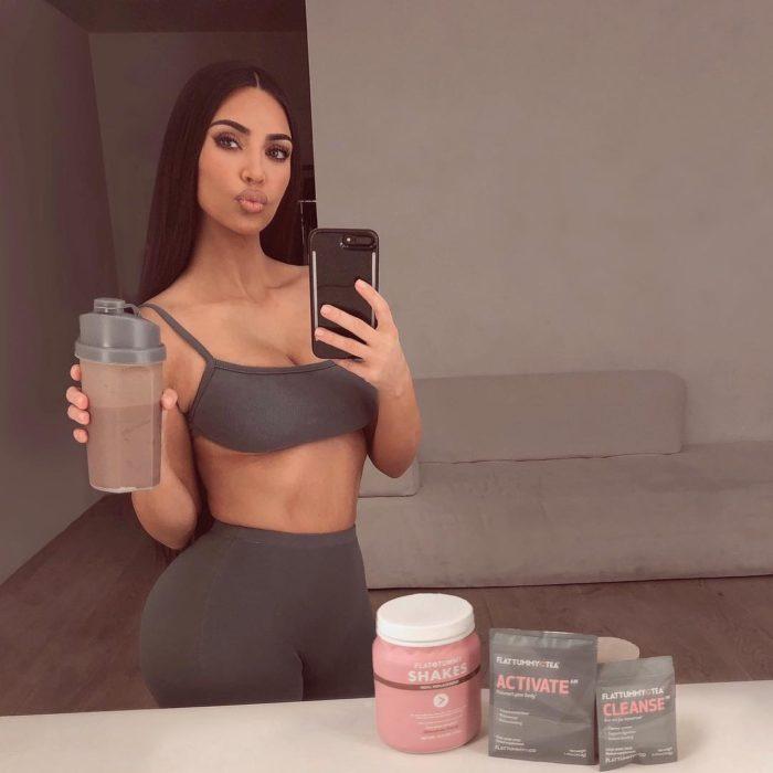 Selfie de Kim Kardashian en ropa deportiva con un vaso con batido para perder peso
