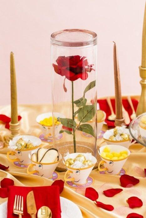 Ideas para quinceañera estilo La Bella y la Bestia de Disney; Chip, la taza, como dulcero; flor dentro de cristal como centro de mesa