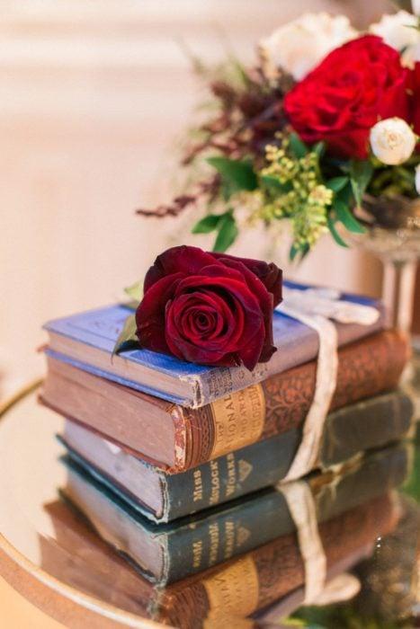 Ideas para quinceañera estilo La Bella y la Bestia de Disney; libros antiguos con una rosa encima