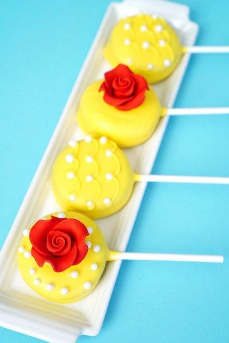 Ideas para quinceañera estilo La Bella y la Bestia de Disney; dulces, galletas cubiertas de chocolate amarillo con adornos de rosas y perlas