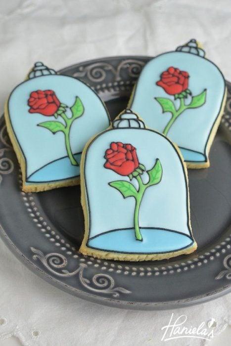 Ideas para quinceañera estilo La Bella y la Bestia de Disney; galletas con forma de rosa dentro de cristal