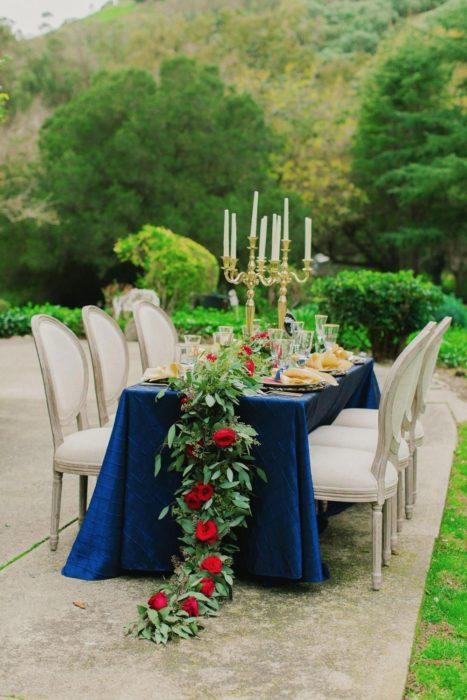 Ideas para quinceañera estilo La Bella y la Bestia de Disney; fiesta al aire libre, mesa con mantel azul y sillas blancas, adornada con flores y candelabros