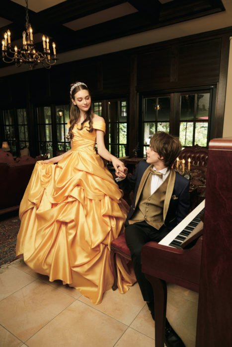 Ideas para quinceañera estilo La Bella y la Bestia de Disney; sesión de fotos de pareja con temática de princesas; mujer con vestido amarillo y tiara, hombre con traje azul y dorado sentado en un piano