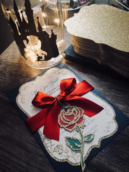 Ideas para quinceañera estilo La Bella y la Bestia de Disney; invitaciones con rosa y moño rojo