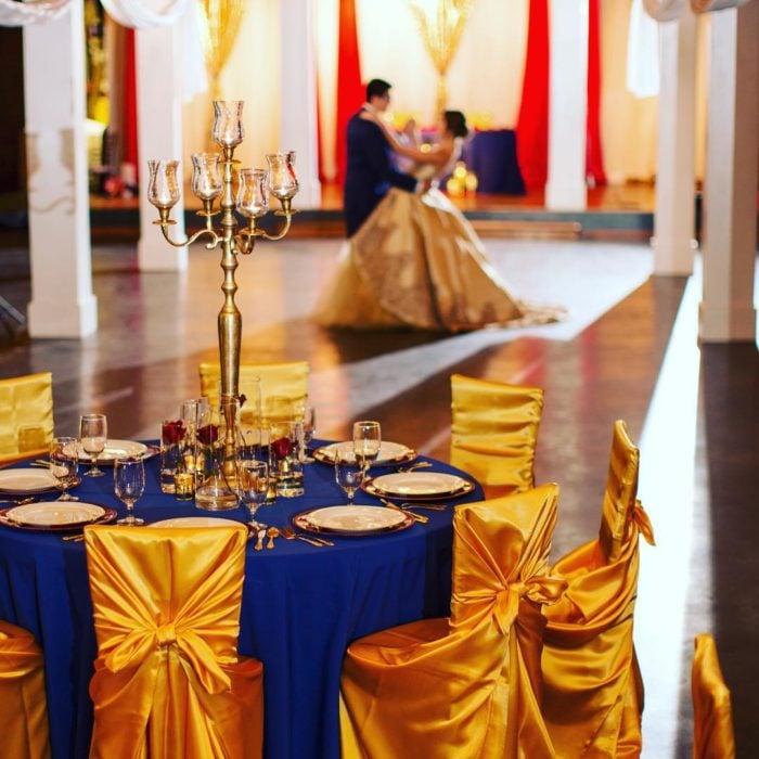 Ideas para quinceañera estilo La Bella y la Bestia de Disney; mesa adornada con mantel azul rey y sillas doradas; pareja bailando