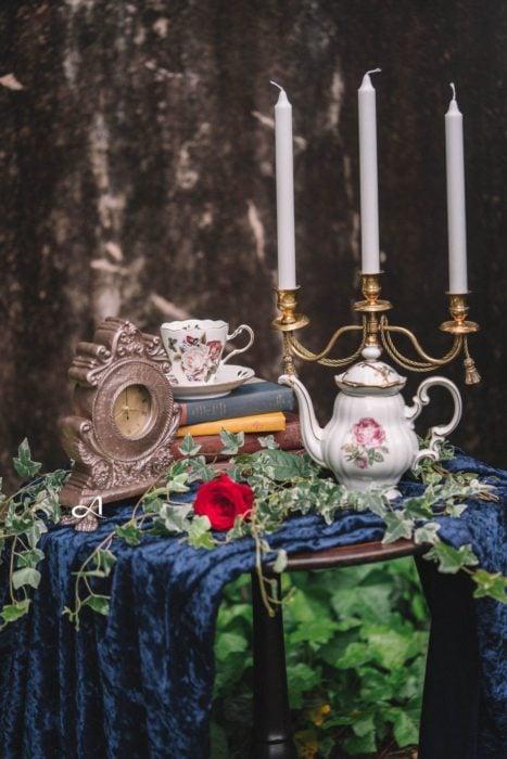 Ideas para quinceañera estilo La Bella y la Bestia de Disney; objetos vintage, reloj, taza, tetera y candelabro, con libros viejos y mantel de terciopelo azul