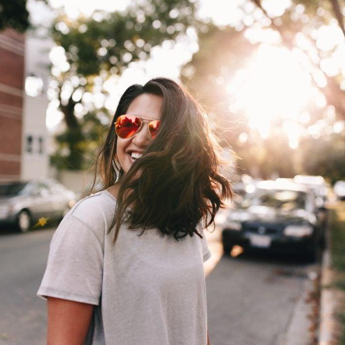 Mujer con gafas rojas a mitad de la avenida durante el atardecer sonriendo y cubriendo su rostro con su propio cabello