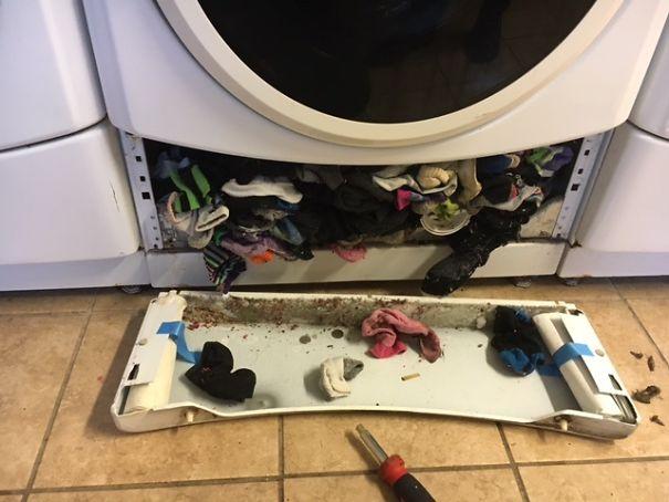 Parte inferior de una lavadora con calcetines, pelusas y dinero ocultos