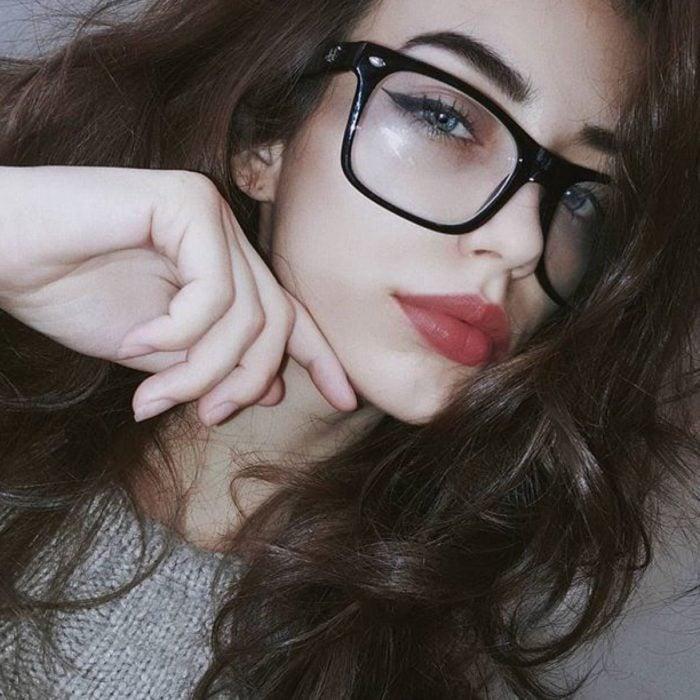 Chica posando para una selfie en la que muestra sus lentes de color negro