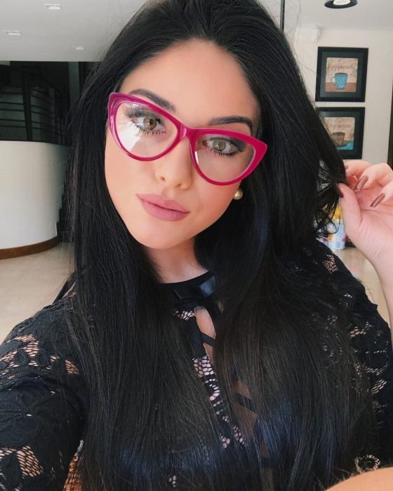 Girl posing for a selfie while showing her pink glasses