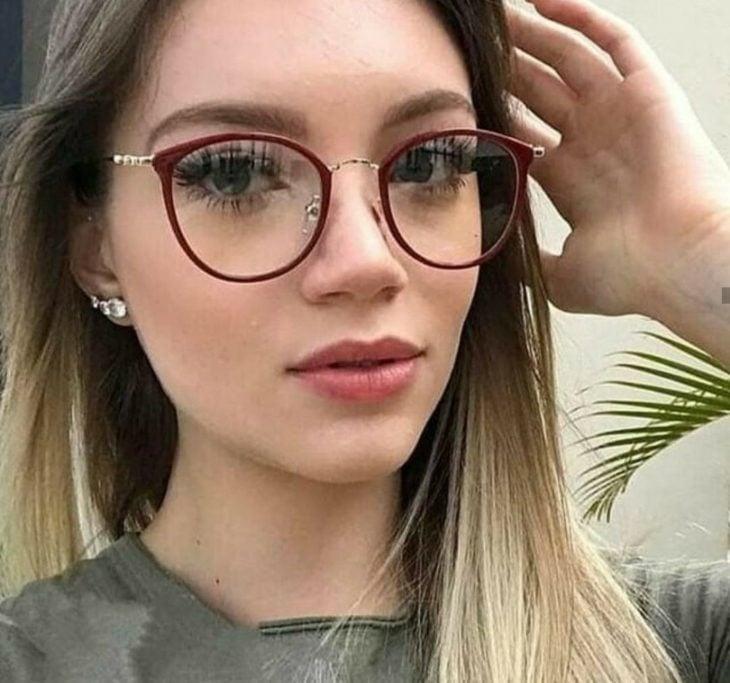 Chica posando para una foto mientras muestra sus gafas redondas de color morado