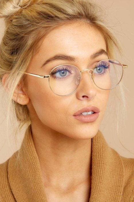 Chica posando para una fotografía en la que muestra sus lentes redondos con transparencias
