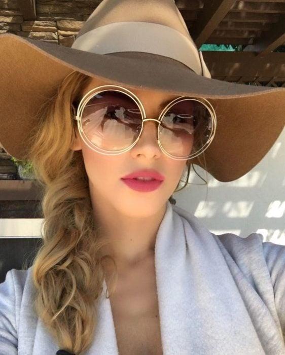 Chica usando gorro de paja y lentes redondos en tono miel