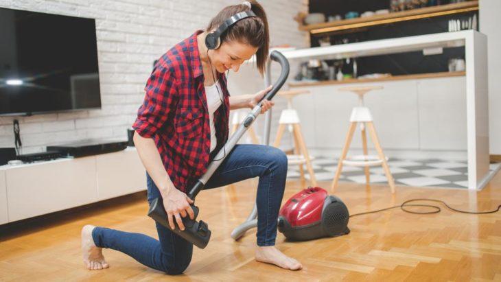 Mujer jugando la aspiradora dentro de la casa