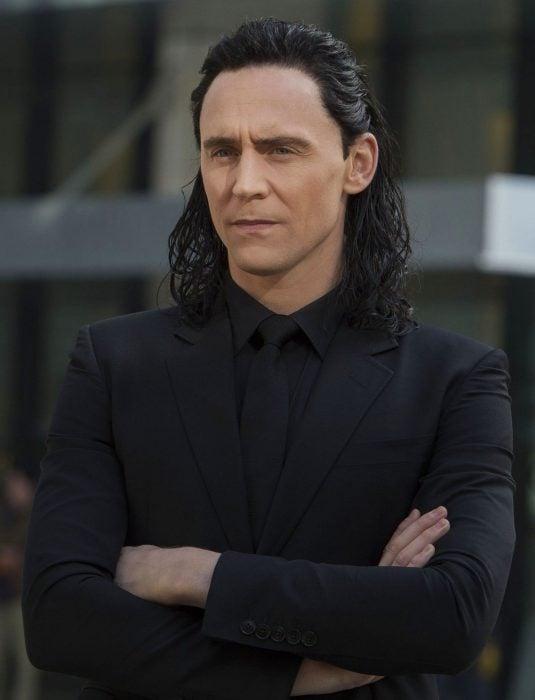 Actor Tom Hiddleston como Loki, hermano de Thor en Avengers, Marvel, hombre de cabello largo y oscuro con traje negro y cruzando los brazos