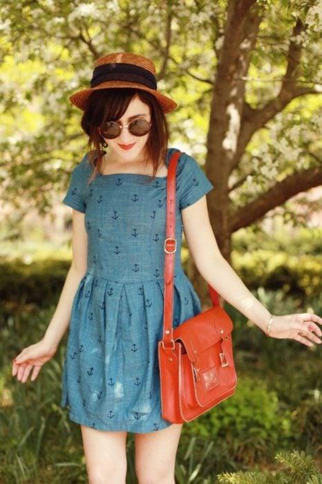 Looks de primavera; chica con vestido azul con anclas, de tela tipo mezclilla, con sombrero, lentes redondos y bolsa roja