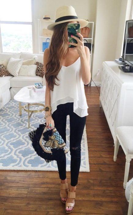 Looks de primavera; chica tomando selfie en su cuarto frente al espejo, con sombrero, blusa blanca sin mangas, pantalón de mezclilla negro y bolso de mano vintage