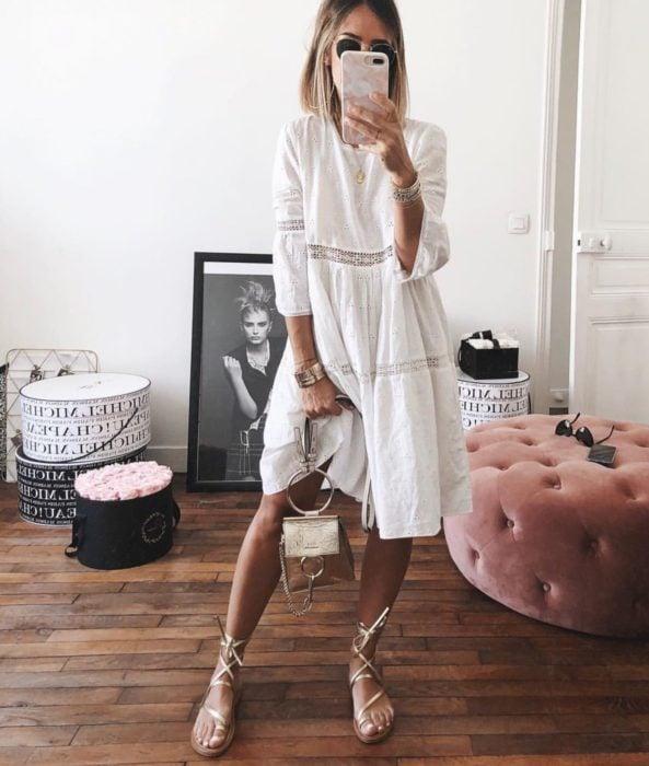 Looks de primavera; mujer de cabello corto y rubio, con vestido blanco de algodón, bolsa de mano y huaraches dorados, tomándose selfie en su cuarto frente al espejo