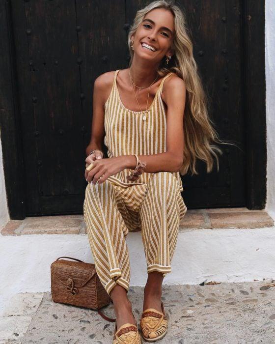 Looks de primavera; mujer bronceada de cabello rubio y largo, sonriendo, usando jumpsuit sin mangas con rayas amarillas y blancas y sandalias y bolso de mimbre
