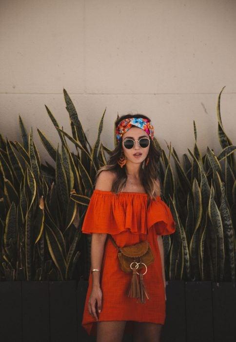Looks de primavera; chica parada frente a plantas, con vestido campesino rojo, lentes de sol y bandana floreada