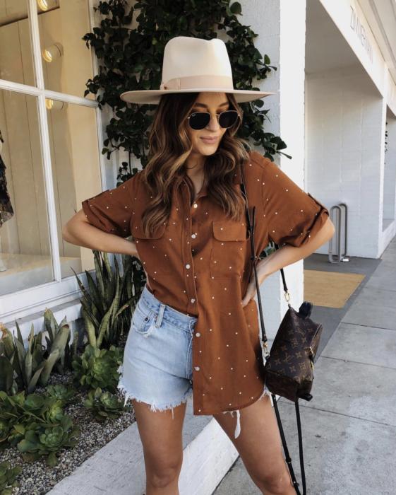 Looks de primavera; chica con camisa café con puntos blancos desfajada, short de mezclilla, sombrero color hueso y lentes de sol