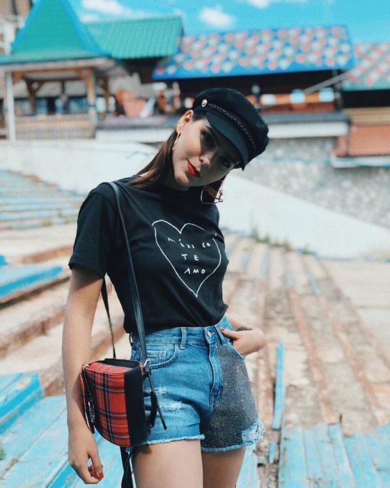 Looks de primavera; youtuber Yuya, con blusa negra con estampado de corazón, short de mezclilla con brillos, mochila con estampado de cuadros escoceses y boina negra