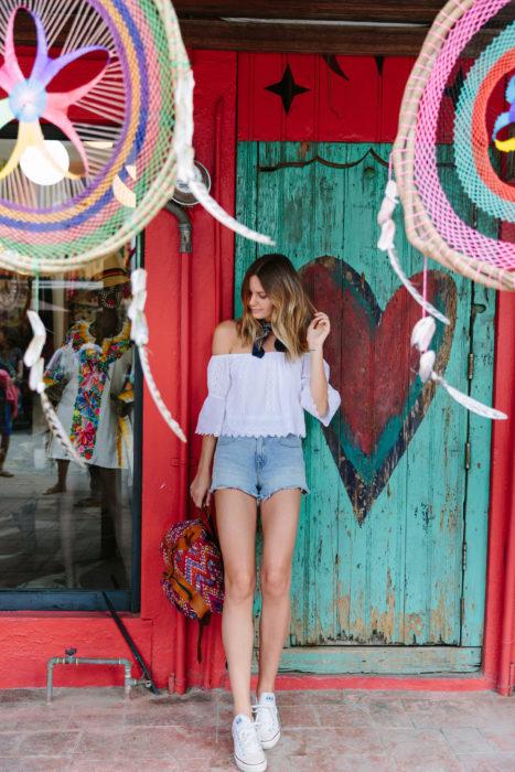 Looks de primavera; chica con cabello rubio ombré, blusa blanca campesina, shorts azules de mezclilla, tenis blancos y mochila tejida; frente a una puerta azul con un corazón pintado