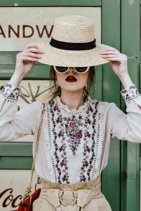 Looks de primavera; chica con sombrero de mimbre, blusa con olanes y flores bordadas, con lentes blancos y labial rojo vino